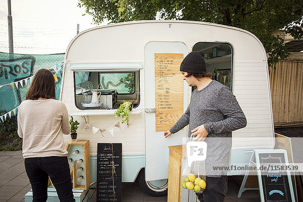 Männlicher und weiblicher Besitzer  der außerhalb des Lebensmittelwagens auf der Straße arbeitet.