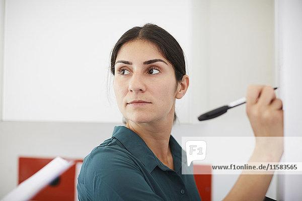 Mittlere erwachsene Geschäftsfrau beim Schreiben auf der Tafel im Büro