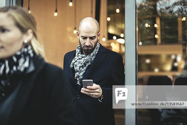 Mittlerer erwachsener Geschäftsmann mit Handy beim Verlassen des Cafés