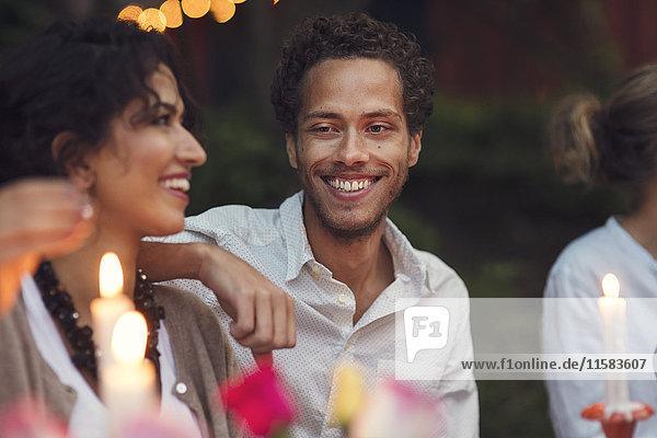 Lächelnde Freunde sitzen auf der Gartenparty