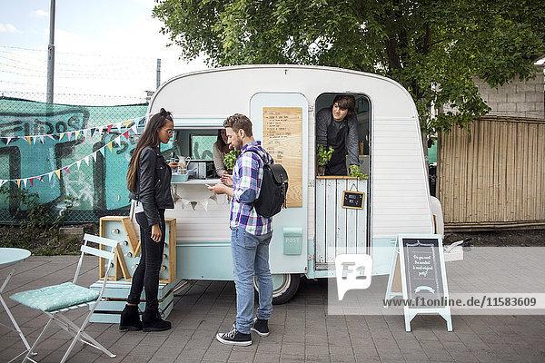 Seitenansicht der Kunden  die vor dem Food-Truck auf der Straße stehen
