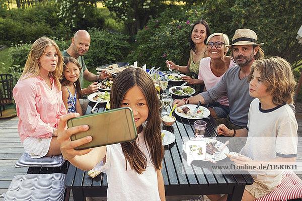 Glückliche Familie und Freunde suchen  während Mädchen  die Selfie vom Handy im Garten während der Gartenparty nehmen.