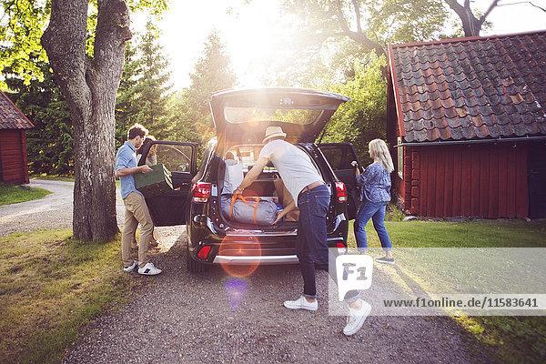 Volle Länge der Freunde beim Verladen des Gepäcks in das Auto an sonnigen Tagen.