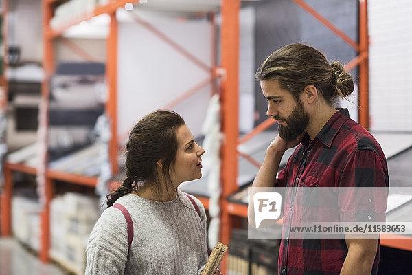 Ein Paar schaut sich an  während es im Baumarkt steht.