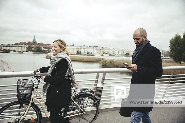 Lächelnde Geschäftsfrau mit Fahrradspaziergang von Geschäftsmann auf Brücke