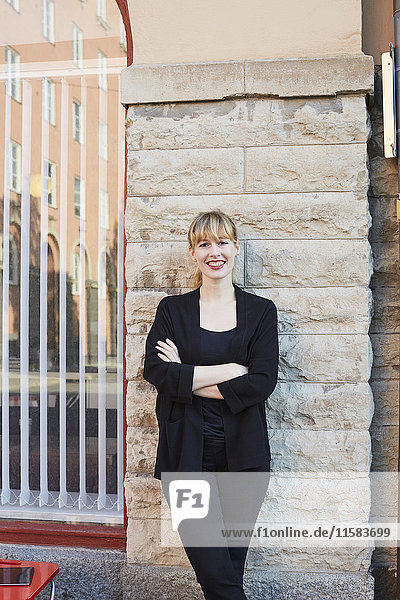 Porträt einer lächelnden Geschäftsfrau mit gekreuzten Armen vor dem Büro