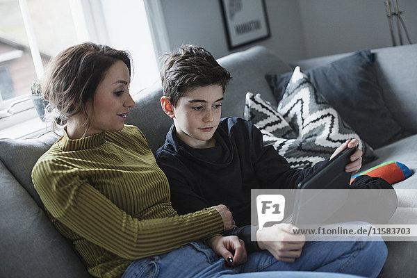 Mutter sieht den Jungen mit dem digitalen Tablett auf dem Sofa im Wohnzimmer an.