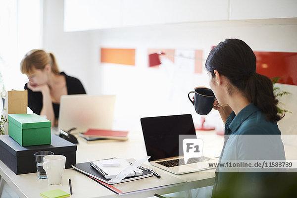 Mittlere erwachsene Geschäftsfrau beim Kaffeetrinken am Tisch mit Kollegin im Hintergrund im Büro