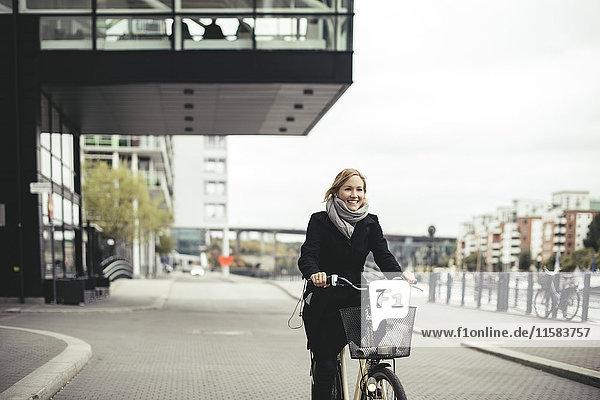Lächelnde Geschäftsfrau mit dem Fahrrad auf der Stadtstraße
