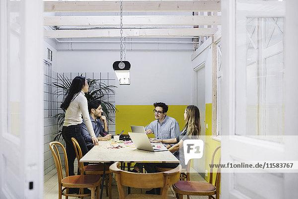 Vier Kreative diskutieren im Vorstandszimmer des Kreativbüros