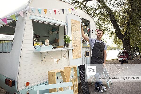 Porträt eines selbstbewussten männlichen Besitzers  der vor einem Food-Truck auf der Straße steht.