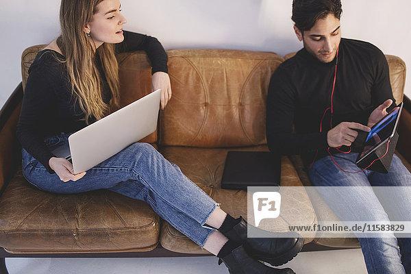 High-Winkel-Ansicht von männlichen und weiblichen Bloggern mit digitalem Tablett  während sie im Büro auf dem Sofa sitzen.