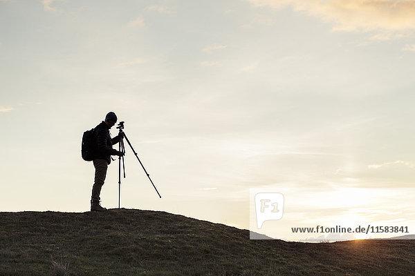 Seitenansicht des Scherenschnitt-Wanderstativs  das bei Sonnenuntergang am Berg gegen den Himmel befestigt wird.