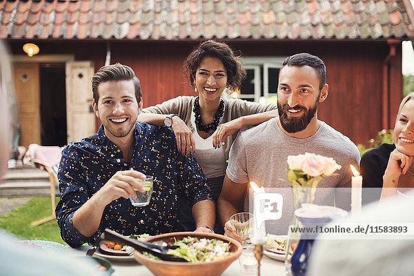 Lächelnde Frau steht mit Freunden am Tisch in der Gartenparty