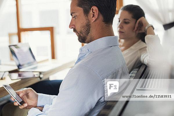 Seitenansicht eines mittelständischen Geschäftsmannes mit Handy von einer Kollegin im Büro