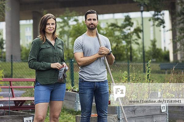 Porträt eines mittleren erwachsenen Paares mit Gartengeräten im Stadtgarten