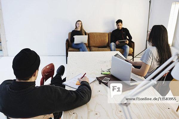 Rückansicht von vier Personen  die mit Kollegen im Kreativbüro diskutieren.