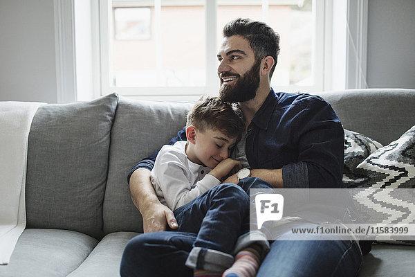 Glücklicher Vater und Sohn beim Sitzen auf dem Sofa zu Hause