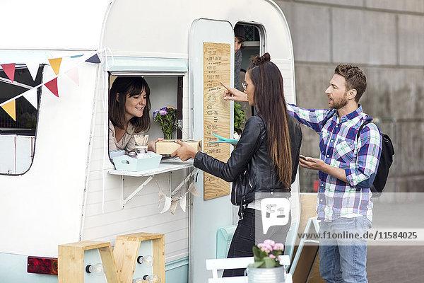 Mann und Frau kaufen Lebensmittel von der Verkäuferin am Food-Truck