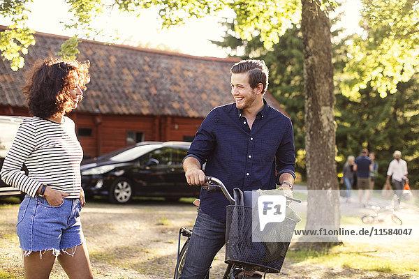 Mann im Gespräch mit einer Freundin beim Radfahren im Hinterhof