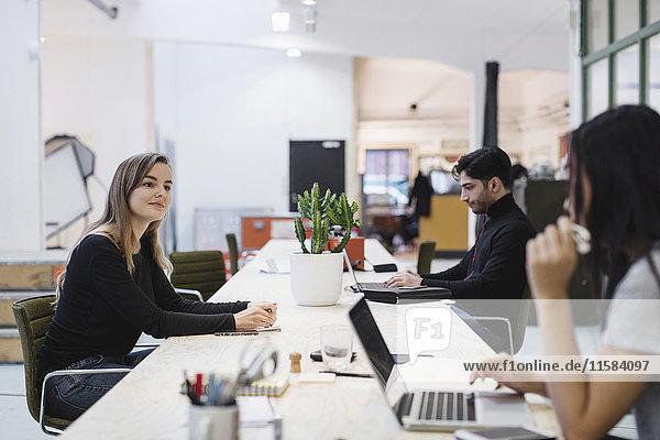 Menschen diskutieren am Schreibtisch im Kreativbüro