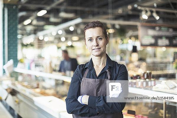 Porträt einer selbstbewussten Besitzerin mit gekreuzten Armen im Supermarkt