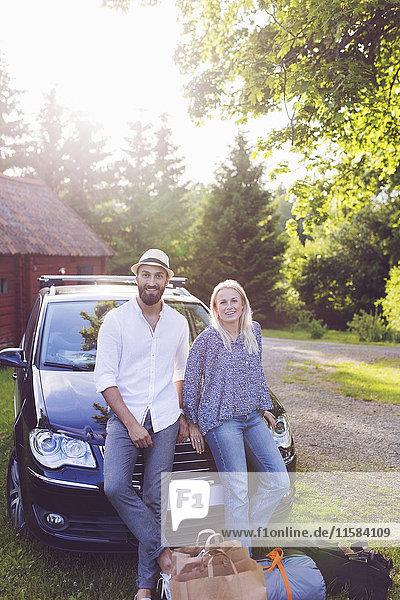 Porträt von Mann und Frau mit Gepäck  das sich an Bäumen anlehnt