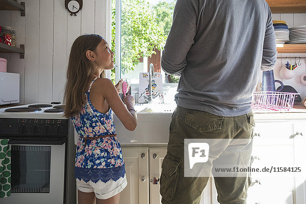 Girl looking at father while standing in kitchen at home