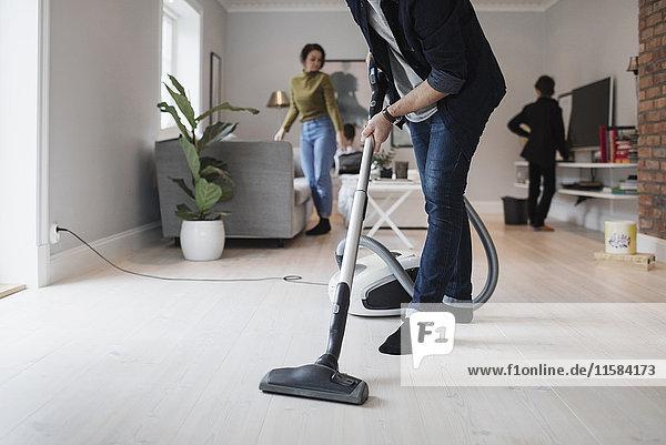 Niedriger Abschnitt des Mannes  der Boden mit Frau und Sohn im Wohnzimmer saugt.