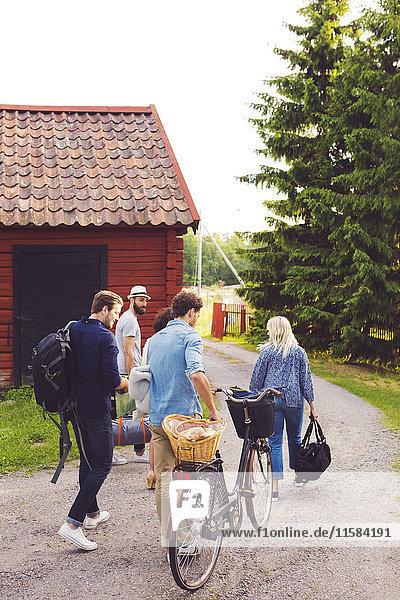Freunde mit Gepäck und Fahrrad zu Fuß auf der Straße durch Hütte