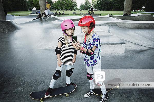 Mädchen zeigt Handy dem Freund im Skateboardpark