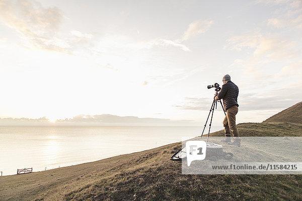Rückansicht des Wanderers  der das Meer durch eine Spiegelreflexkamera fotografiert  während er auf einem Hügel steht.