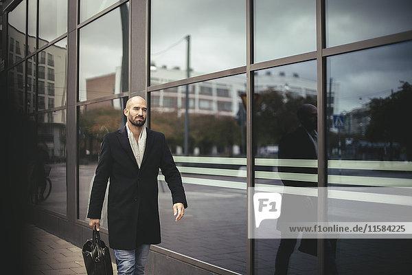 Mittlerer Erwachsener Geschäftsmann mit Aktenkoffer  der gegen das Gebäude in der Stadt läuft.