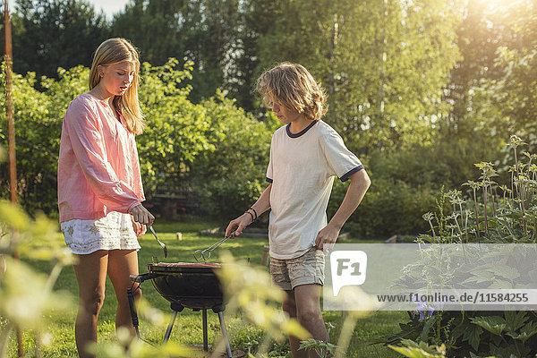 Teenager-Geschwister beim Grillen im Garten an sonnigen Tagen