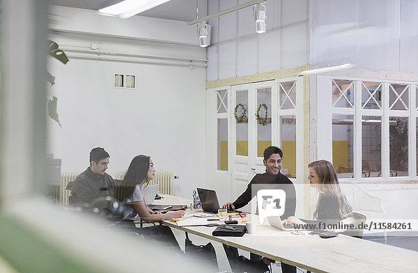 Vier Personen diskutieren im Kreativbüro durch die Glaswand gesehen
