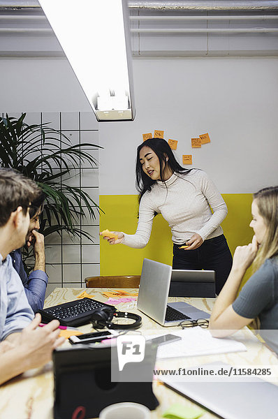 Junge Frau mit Haftnotiz im Gespräch mit Kollegen im Sitzungssaal