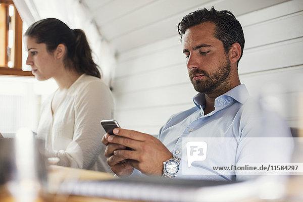 Mittlerer erwachsener Geschäftsmann mit Handy von einer Kollegin im Büro