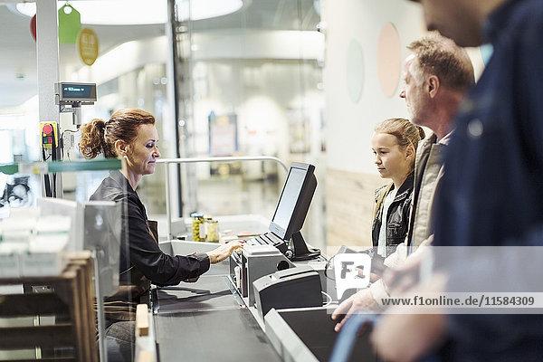 Seitenansicht der Verkäuferin am Computer  während der Kunde an der Kasse im Supermarkt steht.