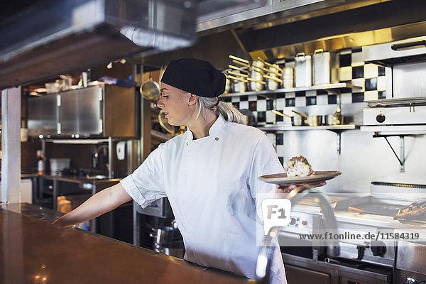Küchenchefin mit Teller in der Küche des Restaurants