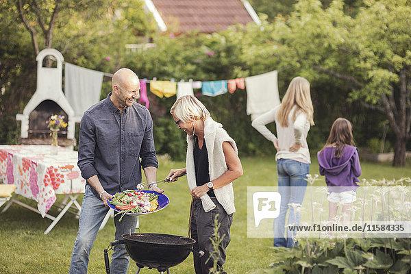 Mann und Frau kochen Gemüse auf dem Grill mit Mädchen  die während der Gartenparty im Garten stehen.