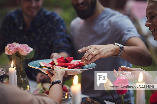 Abgeschnittenes Bild einer Frau  die Wassermelonenscheiben an Freunde auf einer Gartenparty serviert.