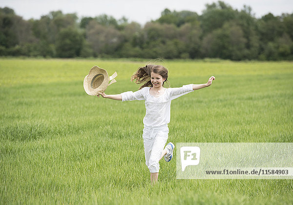 Junges Mädchen springt über Wiese  Frühling