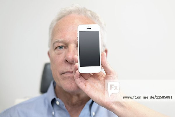 Senior man with smartphone covering eye.