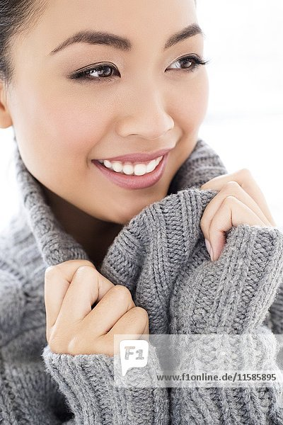 MODEL RELEASED. Young Asian woman wearing grey knitted sweater  portrait.