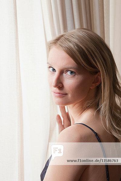 Porträt einer Frau  die aus dem Fenster schaut