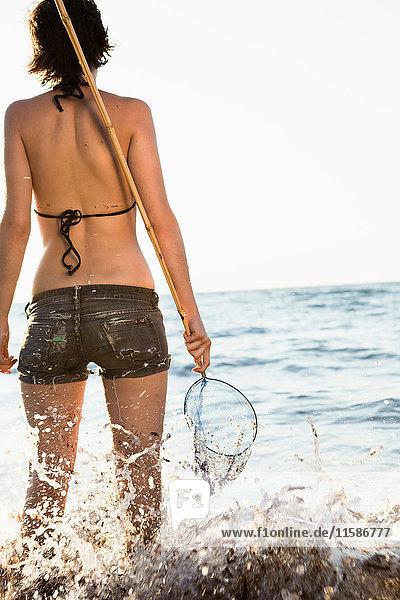 Frau spielt mit Fischernetz am Strand
