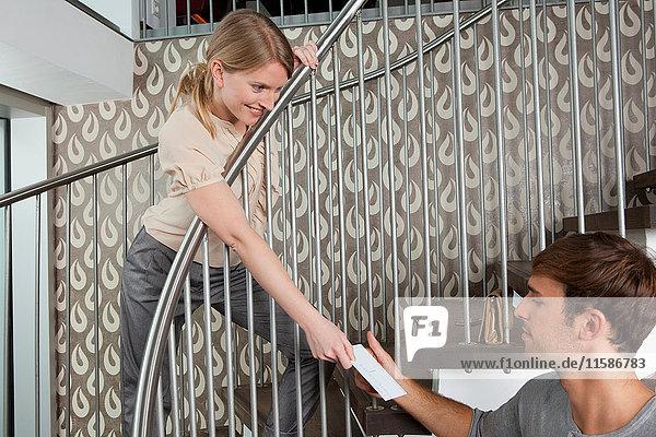 Frau überreicht Postkarte an Freund