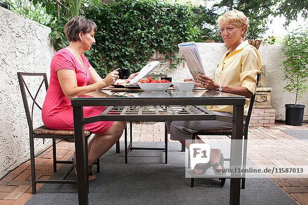 Reifes lesbisches Paar entspannt beim Frühstück im Garten