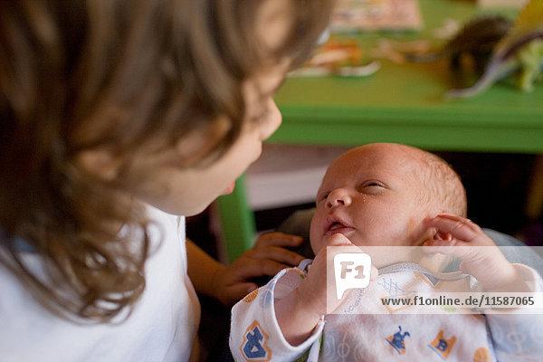 Junges Mädchen mit neugeborenem Bruder auf dem Schoß