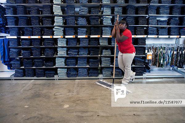Junge Frau lehnt auf Besen in Kleiderladen
